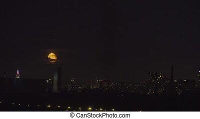 Orange full moon rising above Moscow skyline. - Orange full...