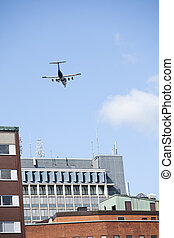 Aeroplane flying close to buildings