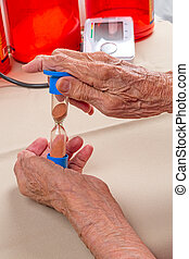 Hourglass in the hands of an old woman - Hourglass in the...