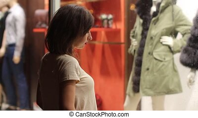young woman looking in shop windows
