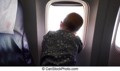 A year-old kid looks out the window of an airplane - A young...