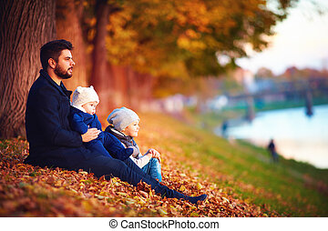 portrait of father with kids enjoying autumn among fallen...