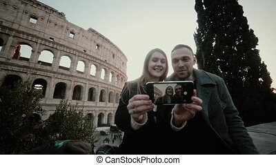 Young beautiful couple sitting near the Colosseum in Rome,...