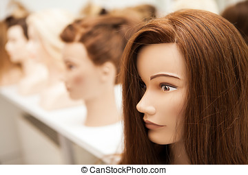 Different mannequin with different hairstyles on a stand....