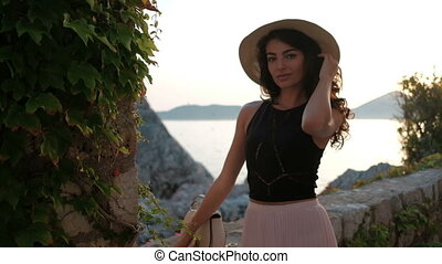Charming brunette woman flirting against the sea and rocks...