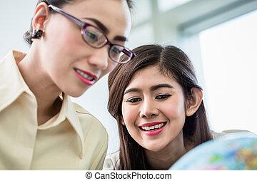Businesswomen planning world dominance in their office -...