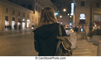 Back view of young tourist woman walking in the city centre...