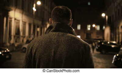Back view of young stylish man walking late at night through...