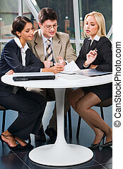 Business team at meeting - Group of three young business...