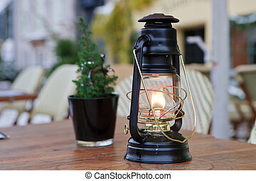 Burning Oil Lamp - Burning black oil lamp on a table with a...