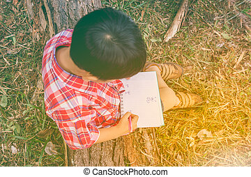 Top view. Boy writing on book. Education concept. Vintage...