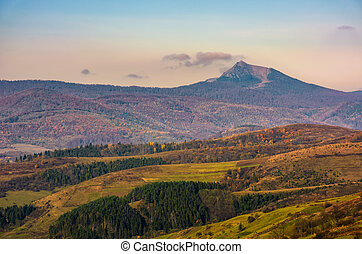 high mountain peak behind the hills with forest and meadows....
