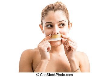 Woman removing facial hair - Cute young Hispanic woman with...