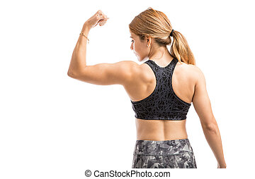 Strong woman in a studio - Rear view of an athletic and...
