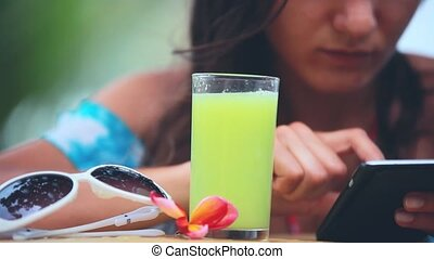 Young attractive woman using mobile phone drinking healthy juice on the beach next to sunglasses and frangipani flower on blurred bokeh background. 1920x1080