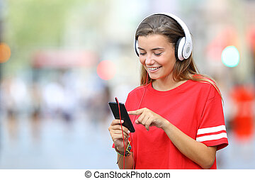 Teen in red listening to music on line on the street -...