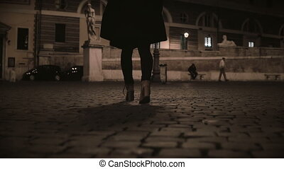 Close-up view of female feet walking through the deserted...