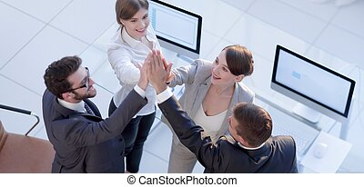 successful business team giving each other a high-five,...