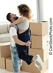 young couple hugging each other in new apartment. - Happy...