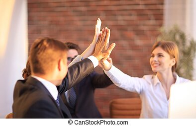 successful business team giving each other a high five. the...