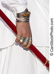 Beautiful man hands decorated with rings holds a saber at...