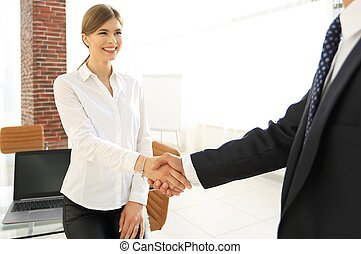 woman Manager welcomes the client with a handshake. the...