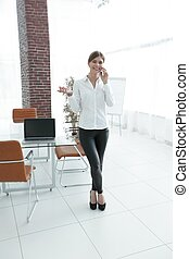 young business woman talking on phone standing in a modern...