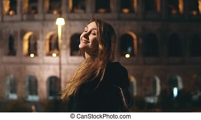 Young beautiful woman standing near the Colosseum in Rome, Italy, looks back in camera and smiling in the evening.