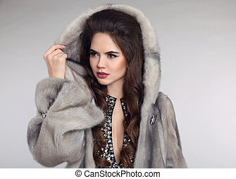 Siberian woman in mink fur coat over studio gray background....
