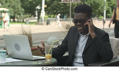Afro-American businessman negotiating by phone, defending...