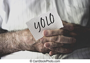 old man with a note with the word yolo - closeup of an old...