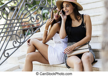 Beautiful women talking on cell phones during summer