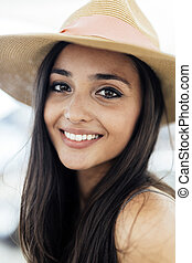 Woman in hat smiling and being truly happy