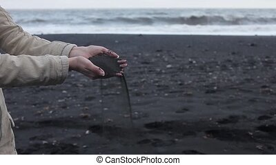Iceland, black sand. Female hands close up, to pour sand...