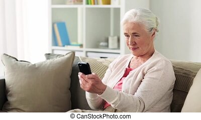 senior woman with smartphone messaging at home - technology,...