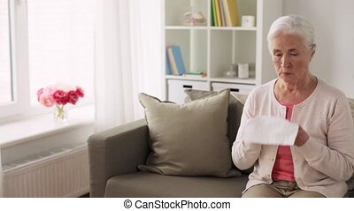 sick senior woman blowing nose to paper napkin - health, old...