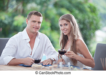 portrait of nice young couple having breakfast in summer environment