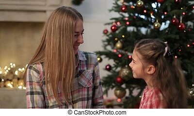 Little girl kissing her mother at Christmas - Portrait of...