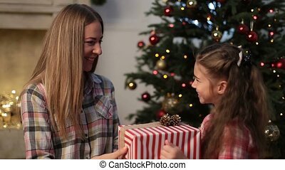 Lovely daughter giving Christmas present to mother - Happy...