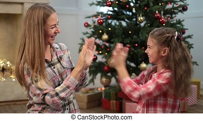 Cute girl playing pat-a-cake with mom on Xmas eve - Excited...