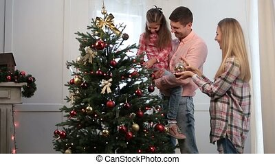 Excited girl decorates Christmas tree with baubles -...