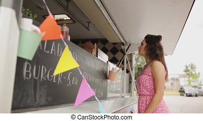 happy young woman buying meal at food truck - street sale,...