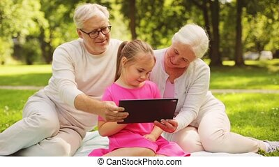 grandparents and granddaughter with tablet pc - family,...