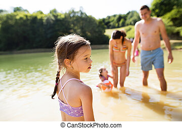 Mother, father and daughters in the lake. Sunny summer. -...
