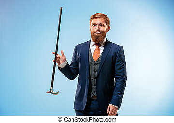 Tattooed bearded man in a suit holding cane. Isolated on a...
