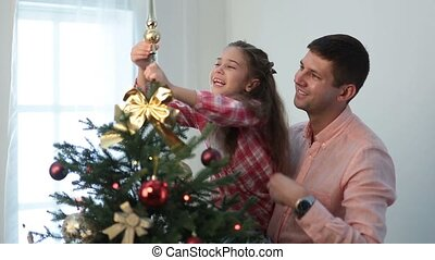 Cute girl putting decorative star on xmas tree top - Smiling...