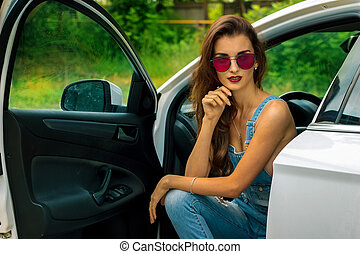 chic young brunette in sunglasses in the car - Portrait of...