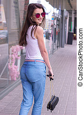 attractive brunette in mirrored sunglasses walking down the...