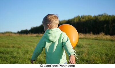 Happy boy plays with balloon in the Park. Walking and outdoor activities