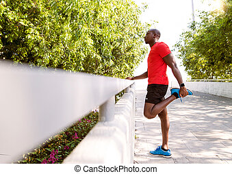 Afro-american runner in the city stretching his legs. -...